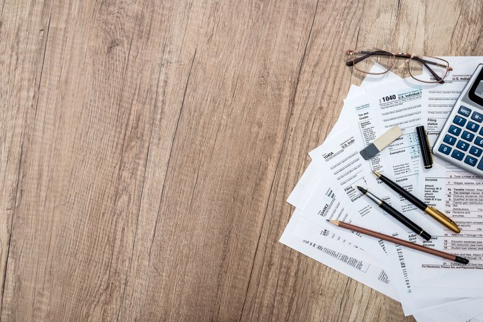 Tax forms with pens, glasses, and calculator on wooden surface