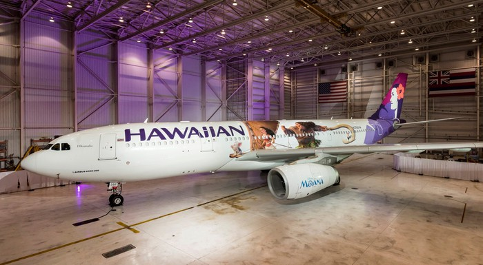 Commercial aircraft with Hawaiian name and logo on it, in a hangar.