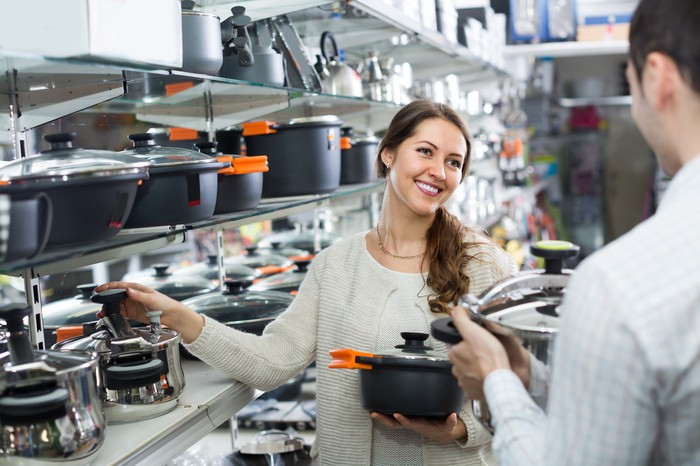 A woman in a store holding cookware.