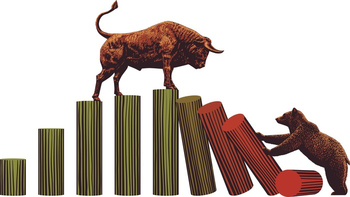Bull standing on blocks as bear knocks them down
