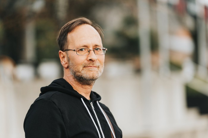 Middle-aged man wearing glasses and black sweatshirt with serious expression