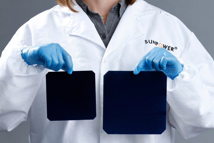 A technician in a lab coat and gloves holding up an A-Series solar cell in one hand and an X-Series in the other