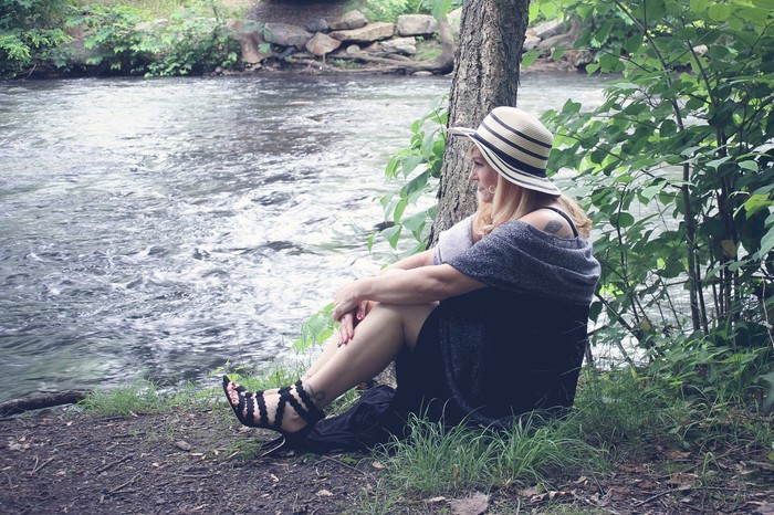 Woman sitting by river in heels