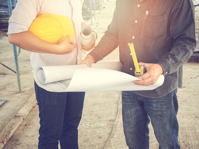 Two men at a construction site, one holding blueprints and the other a hard hat