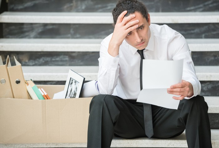 Man sitting on steps, holding head while reading document; next to him is a cardboard box of office supplies.