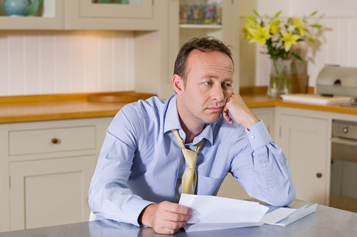 Middle-aged man at table holding documents and looking glum