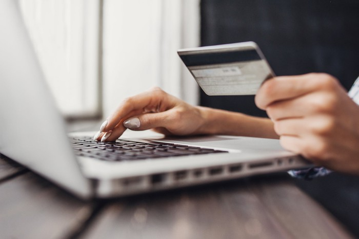 A woman's hand holding a credit card while using a laptop computer.