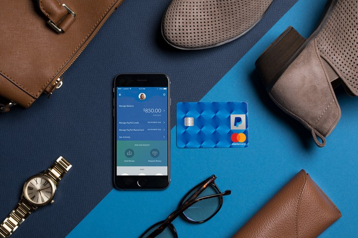 A smartphone displaying the PayPal app next to a PayPal-branded credit card and other luxury items.