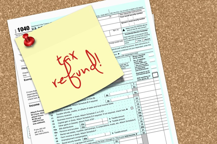 A yellow sticky note reading tax refund is tacked to tax form 1040