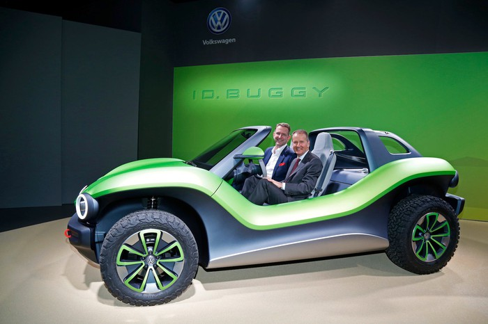 Two executives seated in the VW I.D. Buggy concept vehicle, a futuristic green dune buggy