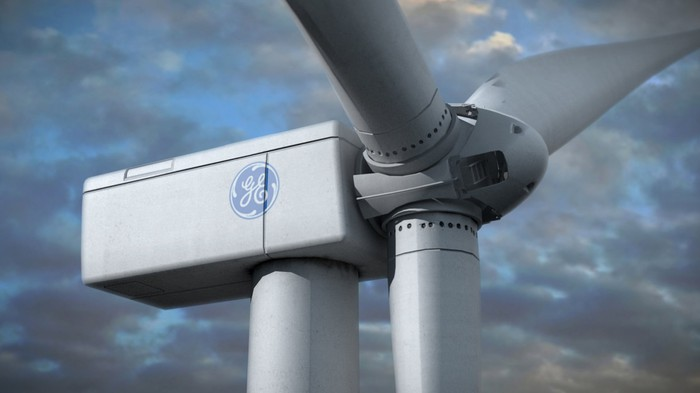 Wind turbine with GE logo on side, on a mostly cloudy day.