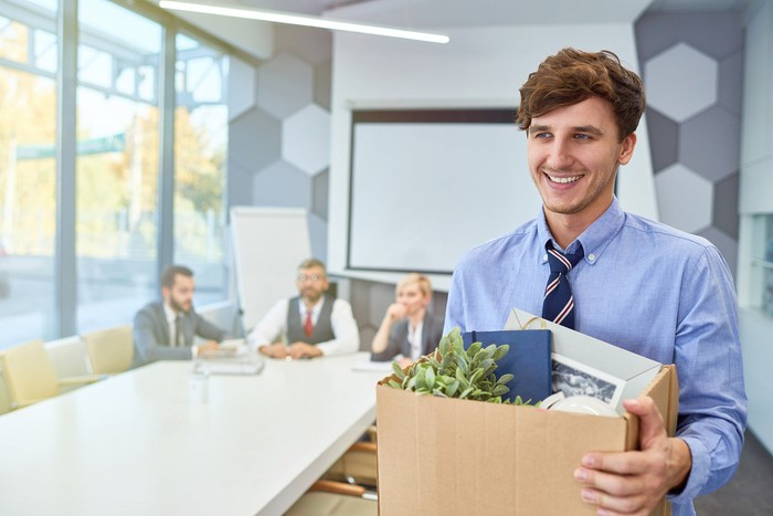 A young man in an office conference room smiles as he carries his office belongings in a box, preparing to walk out.