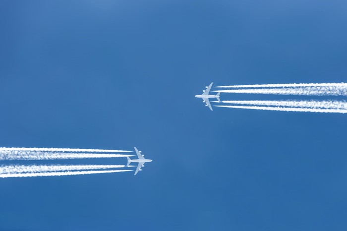 Two planes flying overhead in opposite directions.