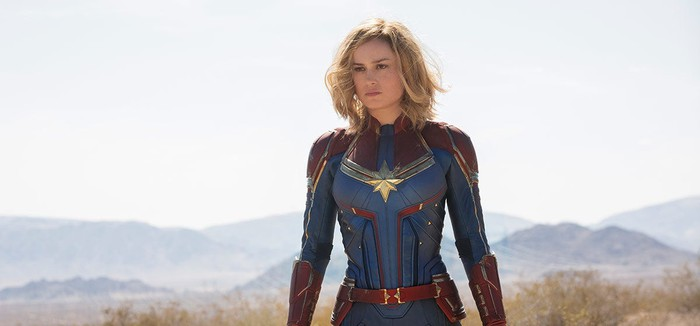A movie still of superhero Captain Marvel in a blue and red outfit with a gold star.