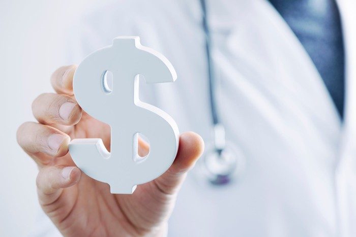 A person in doctor's lab coat with stethoscope hand holding a large white dollar sign.