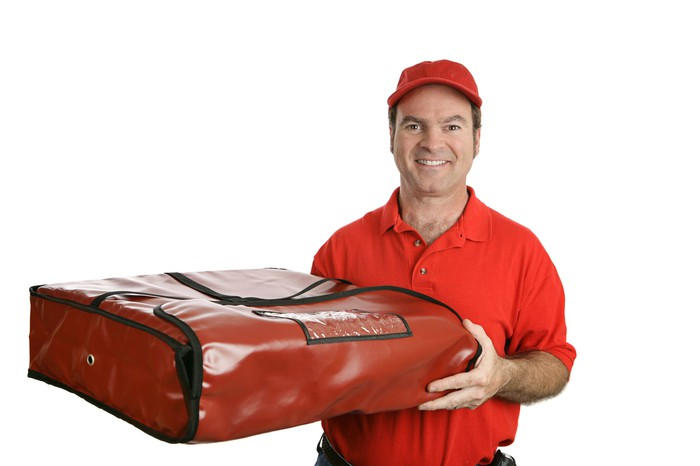 Male in red delivering pizza