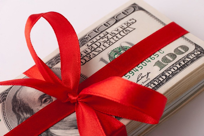 Pile of bills with a red bow around it