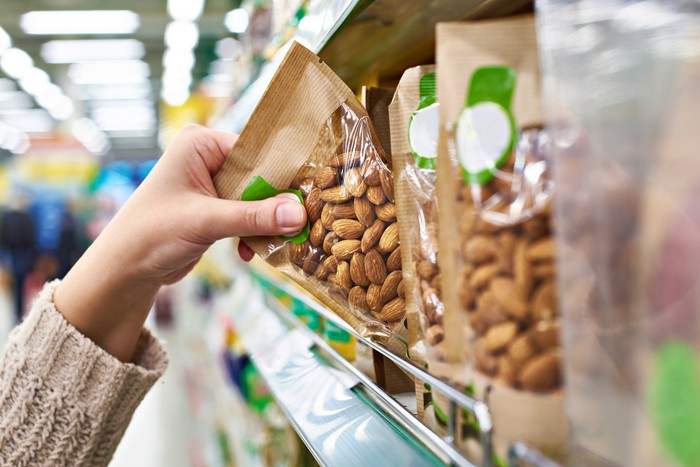 Close-up of a shopper pulling packaged almonds from a grocery shelf.