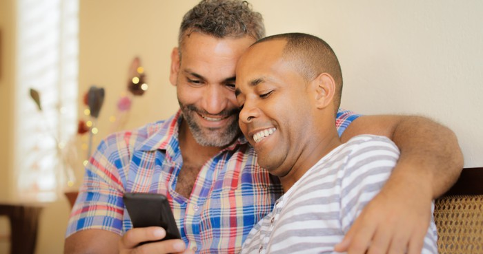Two smiling men on a couch, looking at a phone together