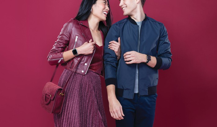 A couple wearing Fitbit Versa Lite Edition devices