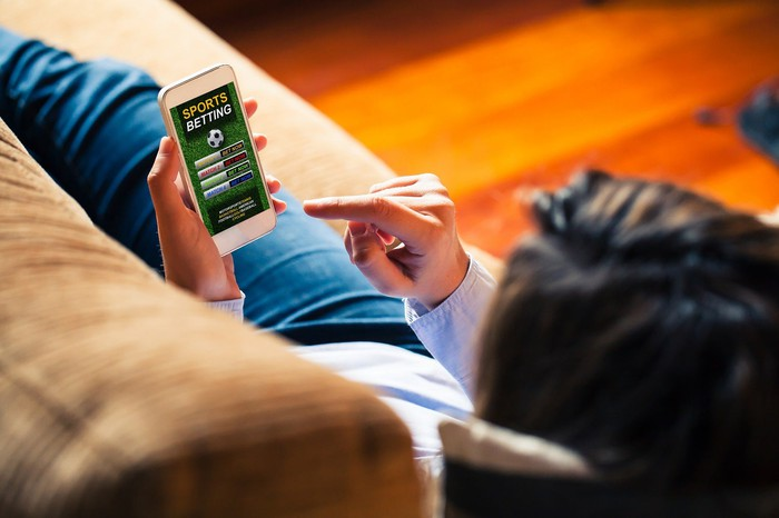 Man making online sports bet on a smartphone.