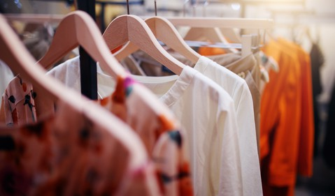 clothing hanging on a rack in a store fashion retail apparel clothes