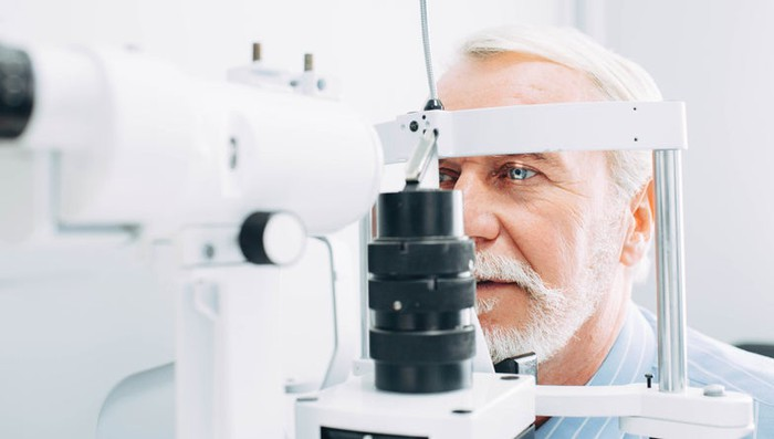 A bearded man's eyes being examined by optometrist or ophthalmologist using a phoropter.