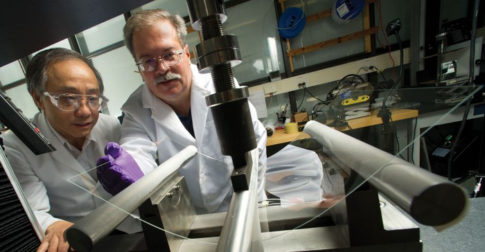 Two scientists in white lab coats bend a sheet of glass for tests.
