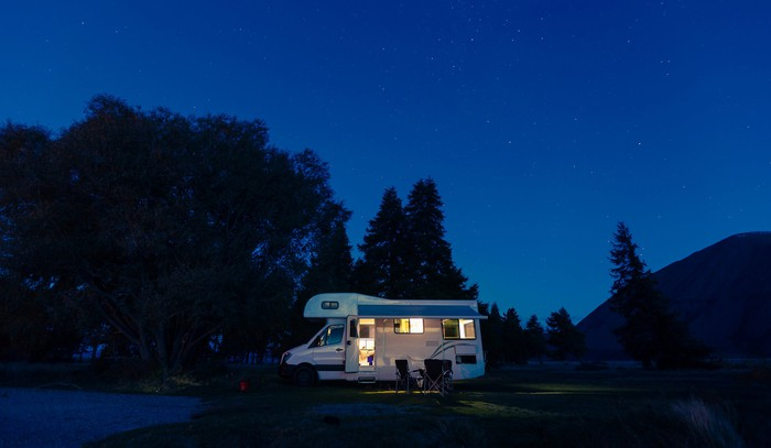 An illuminated RV at night at a mountain campground.