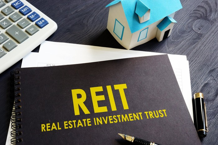 The acronym REIT and the words real estate investment trust on a binder, next to a miniature house, a pen, and a calculator