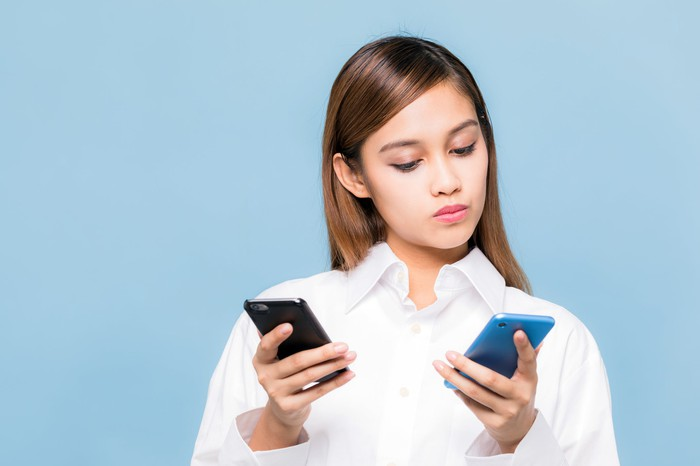Woman looking at two phones.