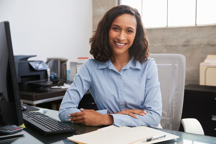A woman sits smiling at an office desk, with a computer and keyboard in front of her.
