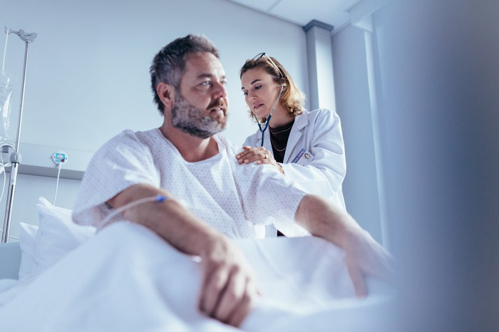 Man in bed being examined by a doctor