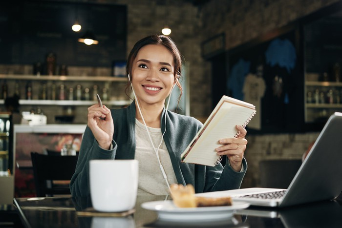 A smiling woman sits at a cafe table, holding a notebook in one hand and a pen in the other.