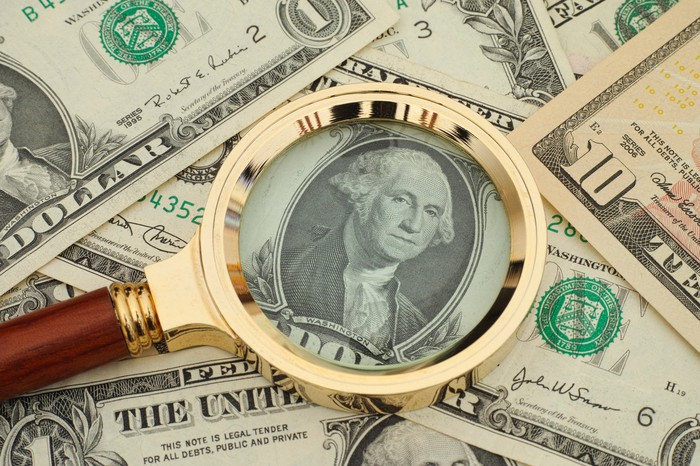 A pile of cash money with a magnifying glass on top of George Washington's image on a dollar bill.