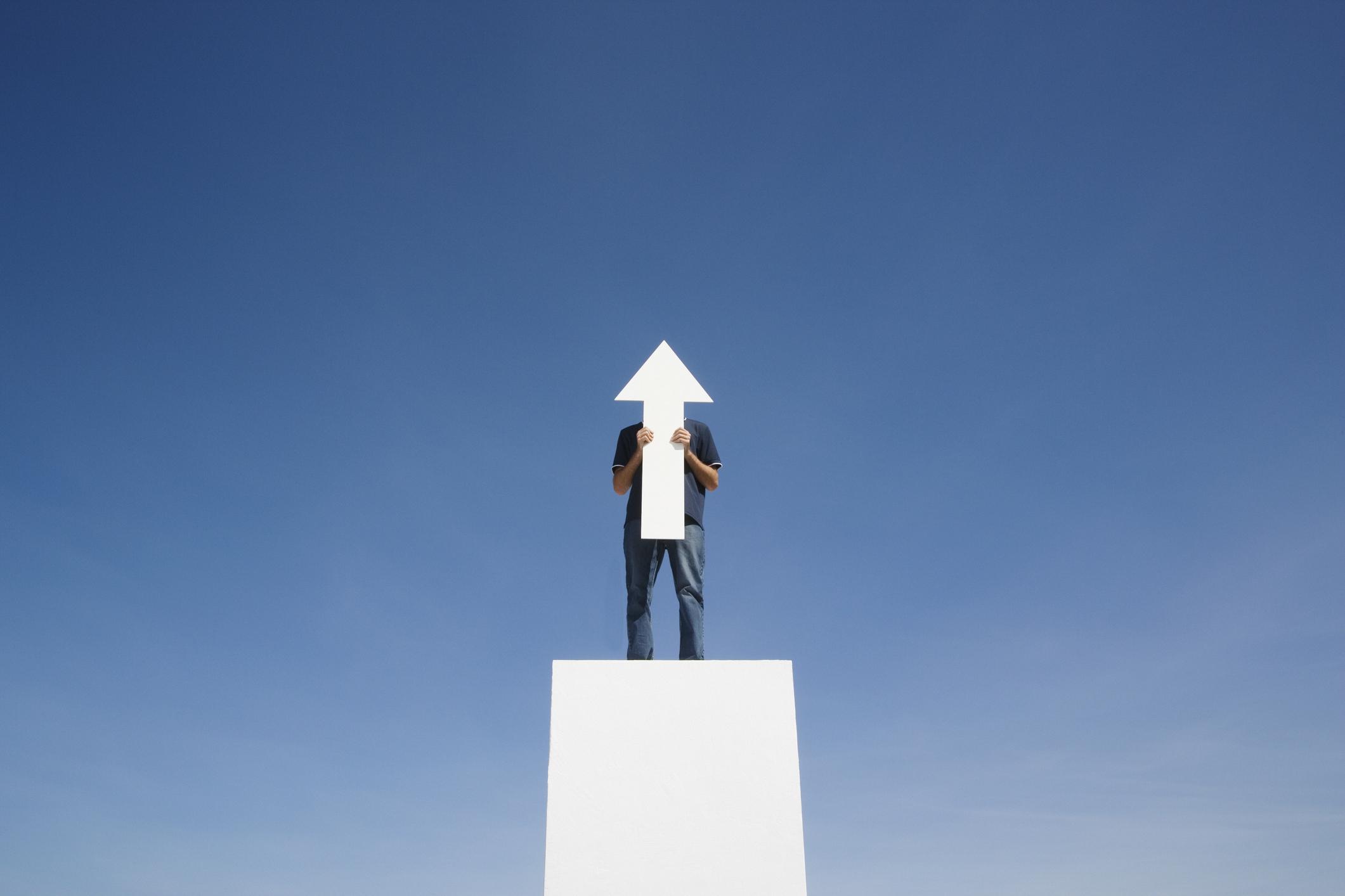 A man holding a cutout arrow pointing upward