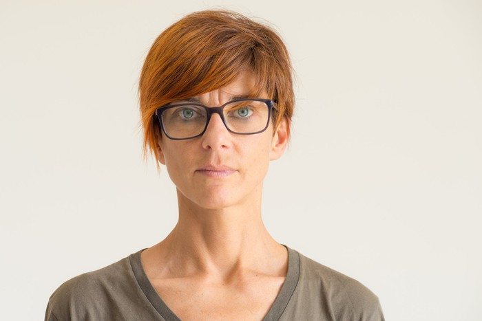 Closeup of woman with short red hair and glasses