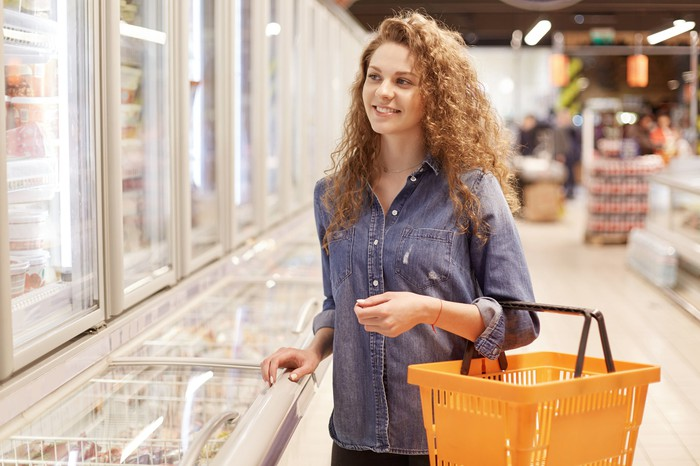 Woman shopping in the freezer section of a warehouse club store.