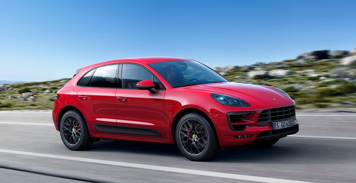 A red Porsche Macan, a sporty compact crossover SUV, on a country road.