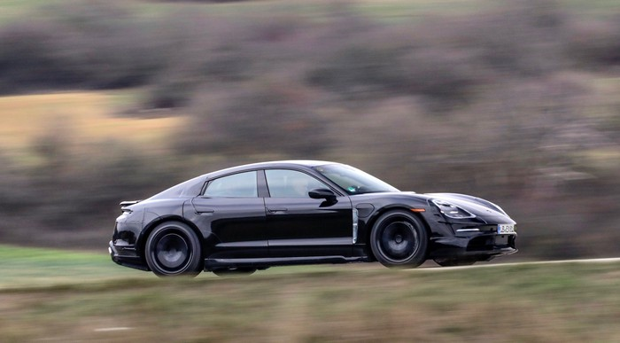 A black Porsche Taycan, a low-slung battery-electric sports sedan, partially covered in fabric to conceal its lines, is shown testing on a country road near Porsche's research center in Weissach, Germany.