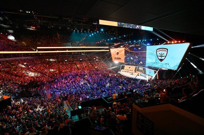 A sold out crowd in a large arena with a brightly lit stage with large screens on the floor of the arena during an esports event.
