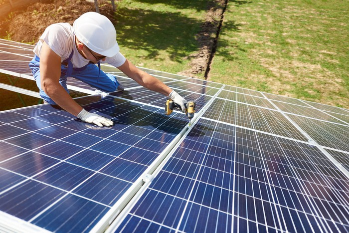 A man in a hard hat uses a drill on a solar panel on a roof