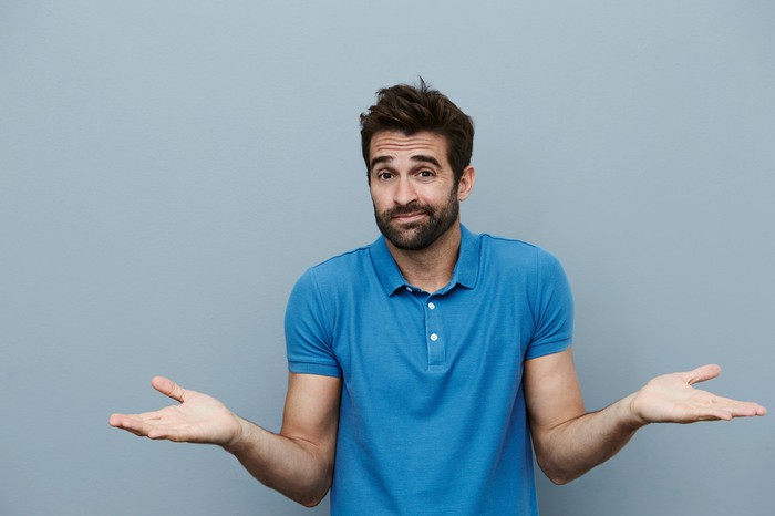 Man in blue polo against gray background shrugging his shoulders