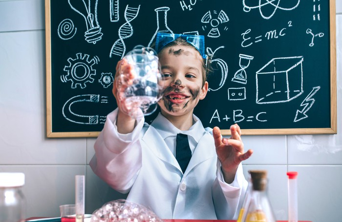 Kid scientist making a mess in a lab with a blackboard in the background filled with science and math drawings.