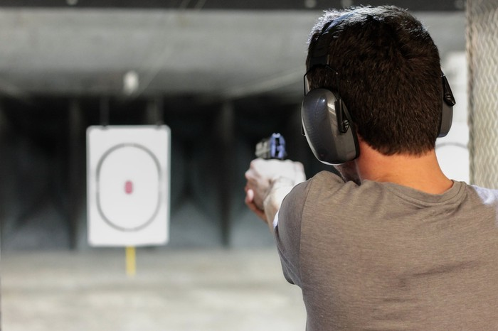 Man firing gun at bulls-eye target.