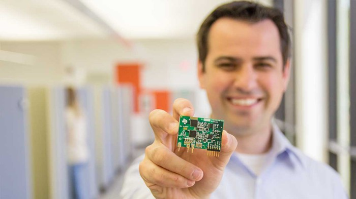 a smiling man holds a microchip in front of him.