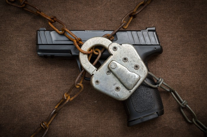 A gun locked by a padlock and chain.