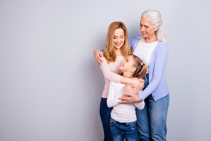Young girl, woman, and older woman embracing