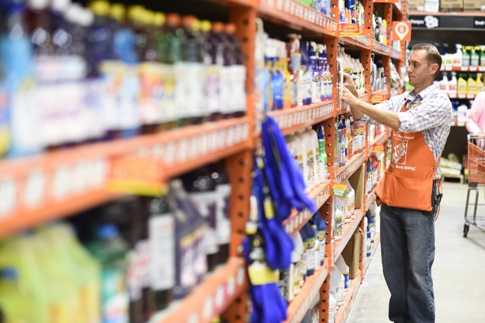 A Home Depot employee rearranges product on a shelf.