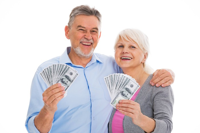 A senior couple standing, holding money in their hands.